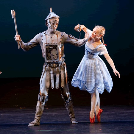 Dorothy helps her friend, the Tin Man, by oiling his rusty joints!