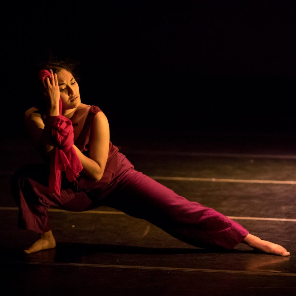 Dancing on stage in low side lunge, a serious look on her face. Photo by Dan Norman