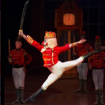 A dancer dressed as the Nutcracker performs a grande sissonne with his sword held high.
