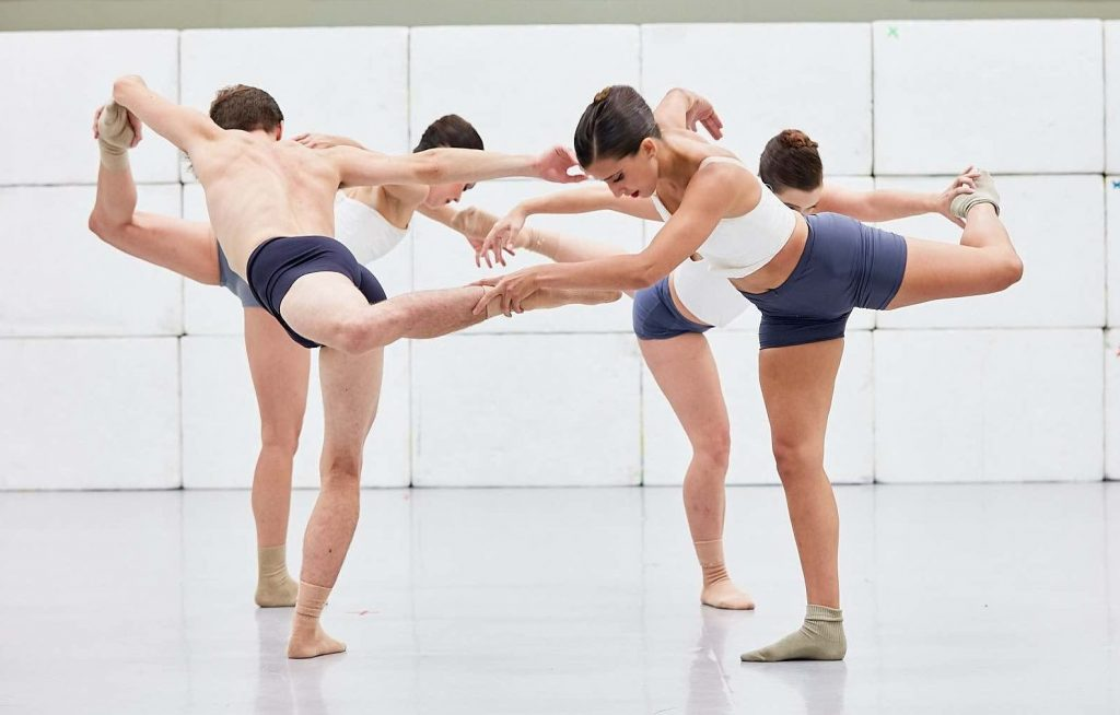 Four dancers form a circle in back attitude, each holding onto foot of the dancer in front of them.