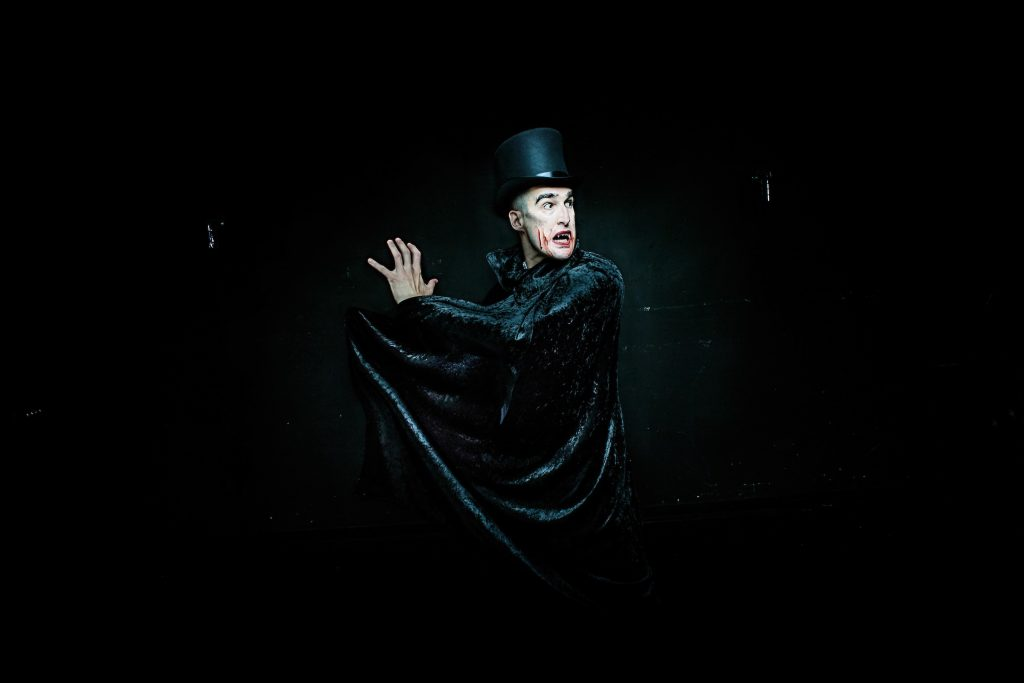 Dracula bares his fangs and sweeps his black cape dramatically.