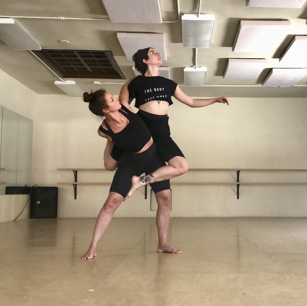 One dancer sits atop another, both dressed in black. Their arms and legs are intertwined.